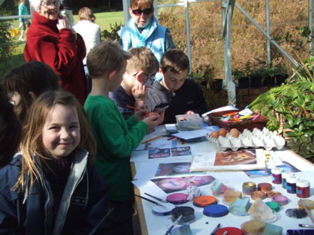 Young artists getting creative with egg and facepainting.